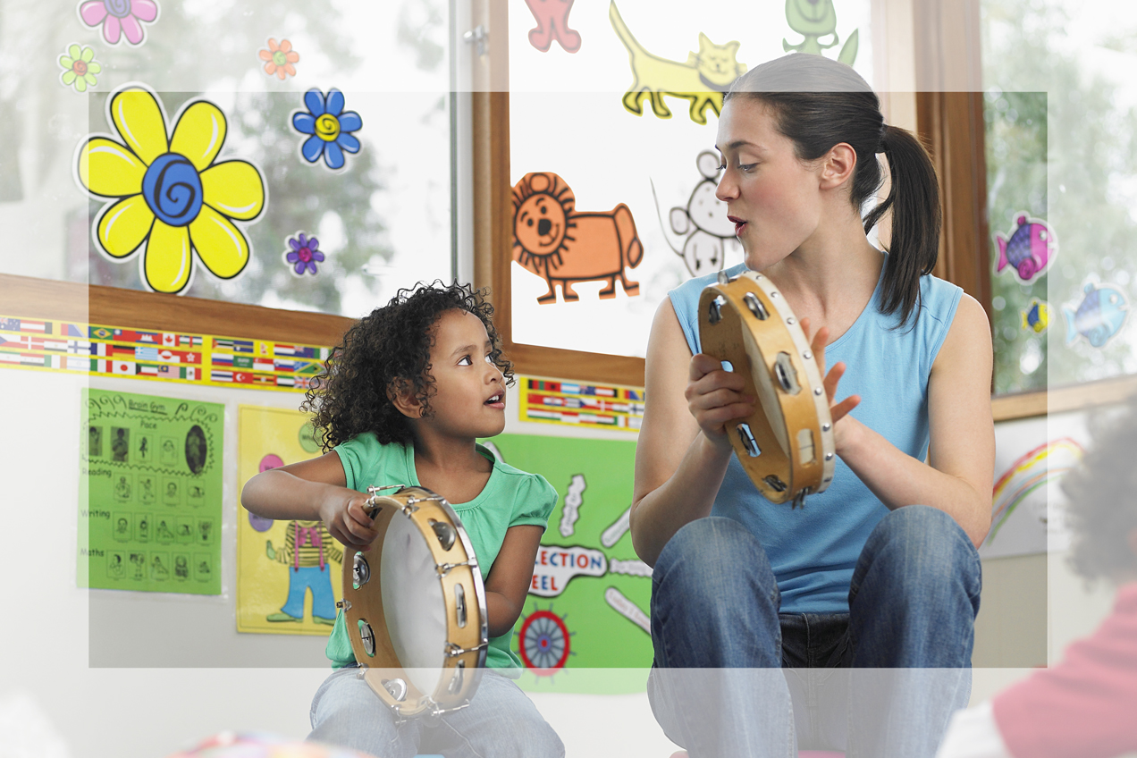 Child care provider playing tambourine with child
